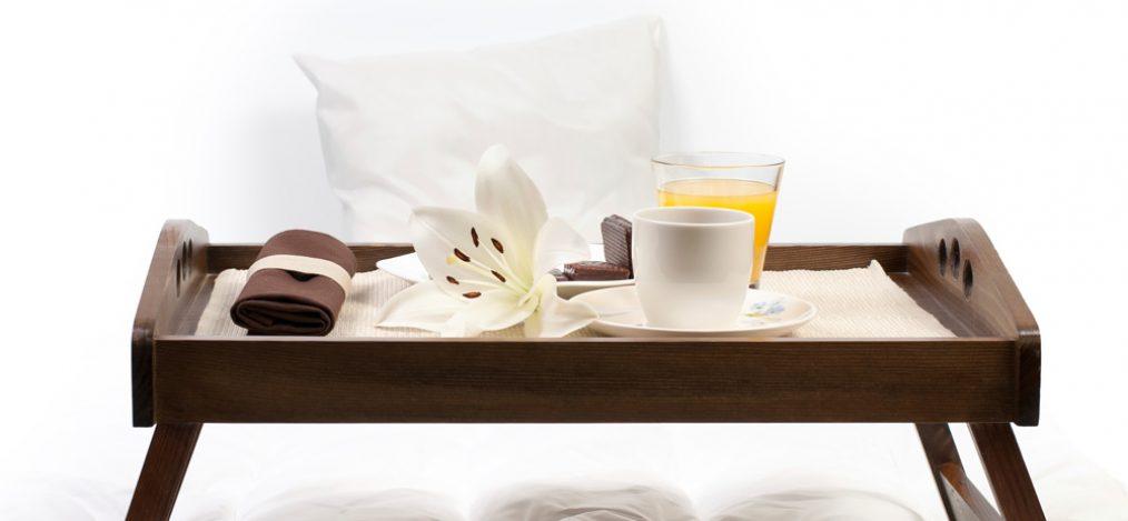 Braunes Holztablett auf Bett