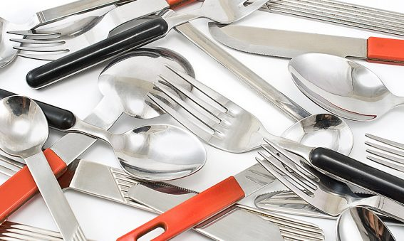 Mehrere Löffel, Gabel, Messer liegen auf Tisch