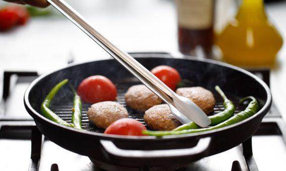 Küchenzange wendet Gemüse in Pfanne