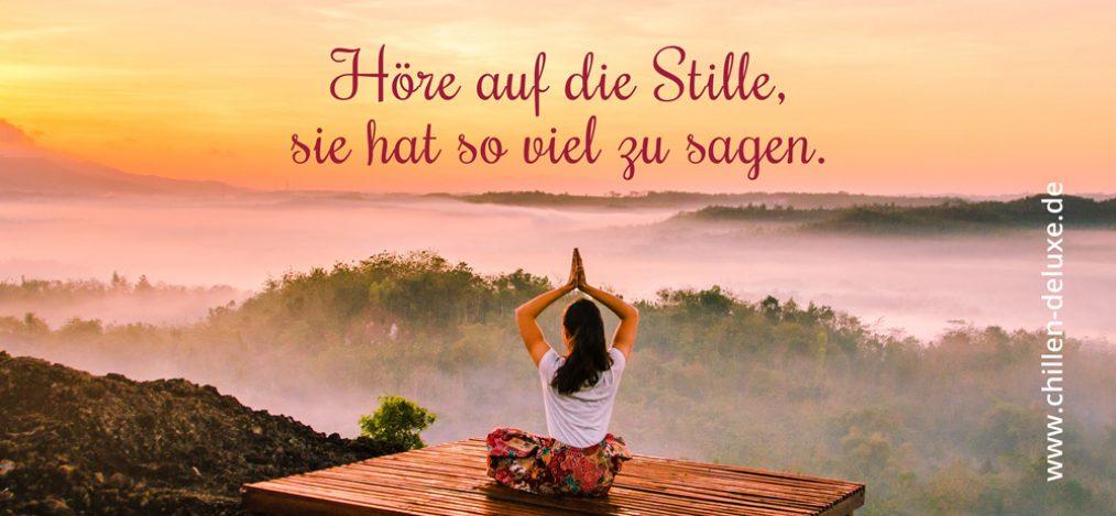 Postkarte: Frau sitzt auf einem Aussichtspunkt und meditiert